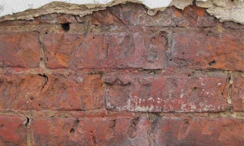 Cracked Plastered Brick Wall